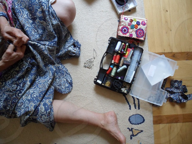 high angle photo of person sewing blue and brown paisley dress beside black and white plastic sewing kit photo