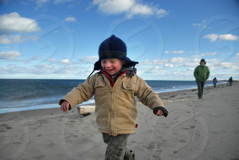 A happy little boy running on the beach in the fall with a hat and jacket with his Mum in the background. photo