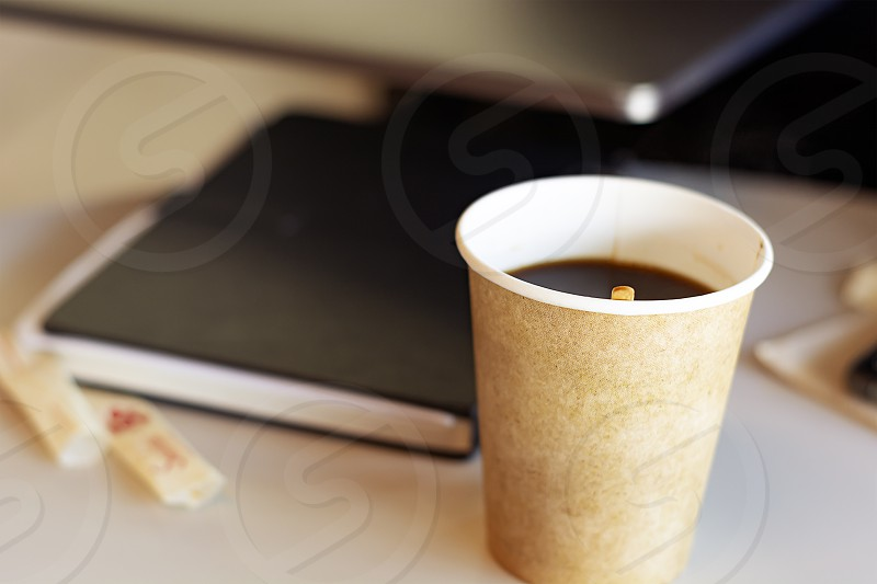 Hot coffee in a recycled paper container. Coffee break in the office. Closed book on the blurred background photo