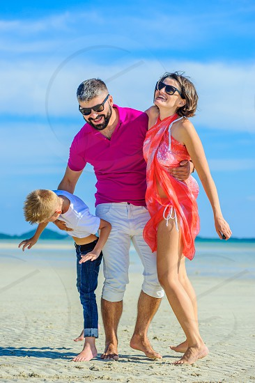 Happy family of three at the tropical beach laughing and enjoing time together. photo
