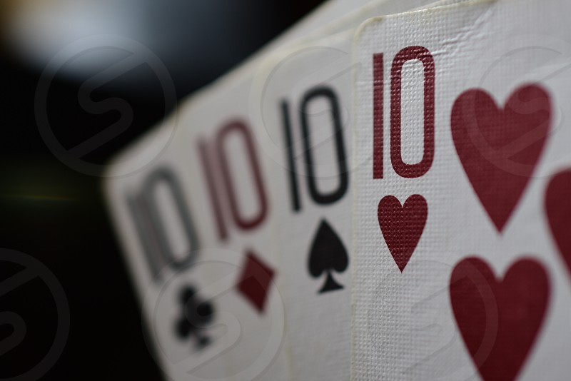10 of hearts 10 of ace 10 of diamond and 10 of clubs arrange alternately by their color photo