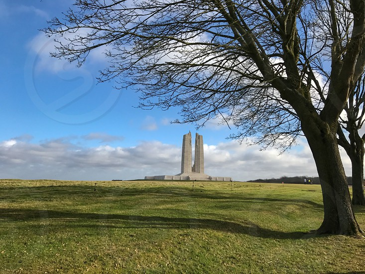 Outdoor day landscape horizontal colour Vimy Ridge France Europe European Battle of Arras Western Front World War One WWI WW1 First World War battleground trees shell holes shell shells weapon weaponry artillery explosion explosives explosions green grass sun shine shining war warfare trench Trenches memorial remembrance commemoration white marble stone carved Canada Canadian field photo