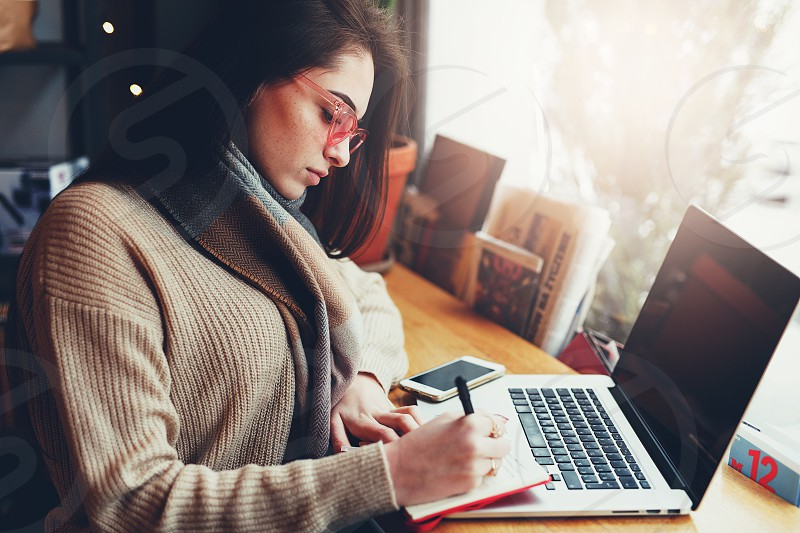 Pretty brunette woman do her work at cafe wear glasses and chat in laptop near the window. - Image photo