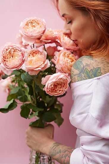 Wonderful summer fresh roses living coral colored as a greeting bouquet in a female's hand with tattoo on a coral background. Place for text. Gift for Mother's Day. photo