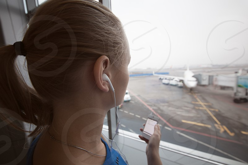 Woman in headphones by the window at aiport listening to music using smart phone. Entertainment during flight waiting photo