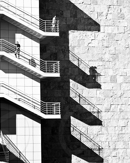 Two people stand at different levels on the outside stairs of a large building the shadow of one person appears on the building's exterior wall. photo