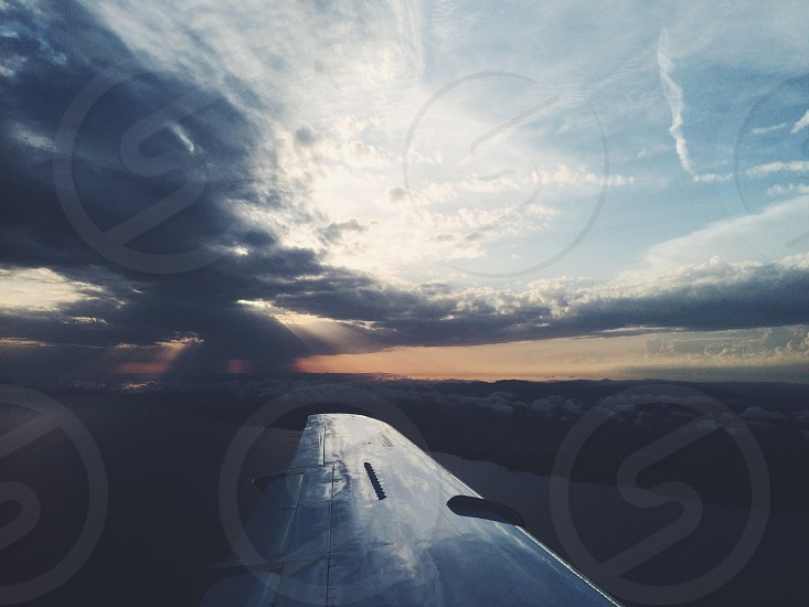 silver airplane wing in mid air across gray clouds photo