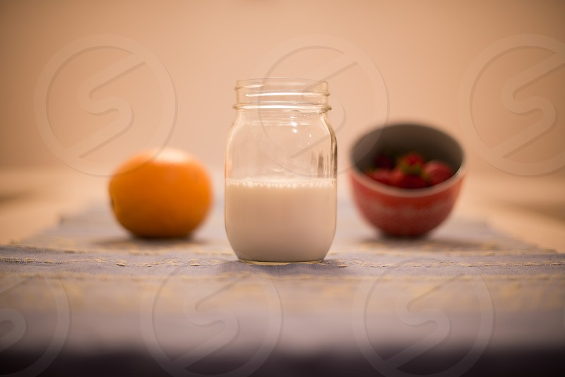 orange milk and berries on a table photo