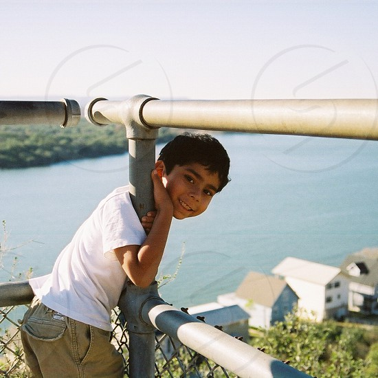 boy in white t shirt hugging a grey steel tube fence photo