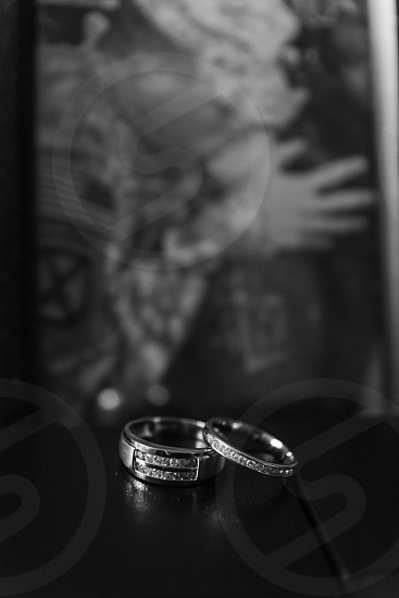 Wedding rings in front of picture of the couple to be with groom in military attire photo