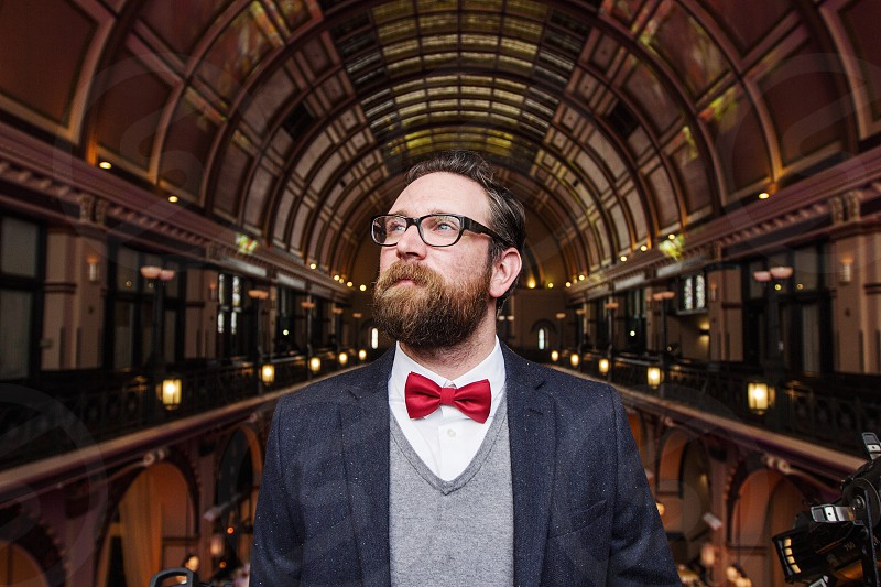 bearded man in grey sweater and black coat with red bowtie in arched room photo