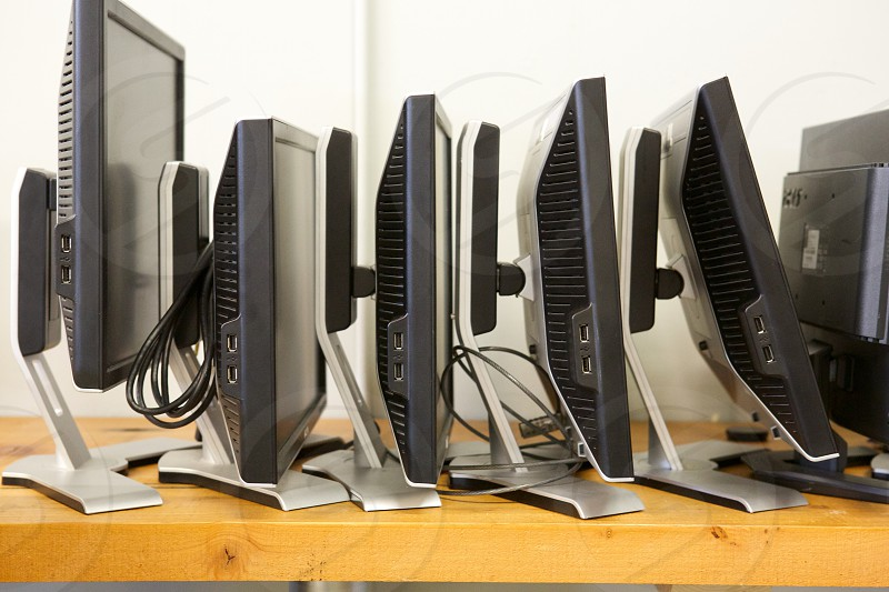 A pile of computer screens at the office.  photo