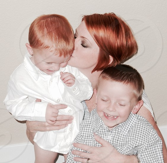 woman with red hair holding two boys photo