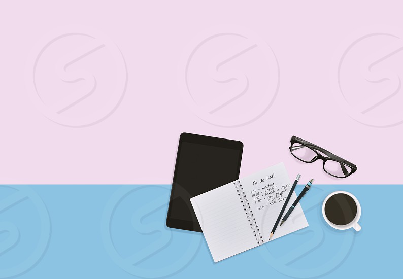 Personal business man workspace desktop in pastel color background with notes in notebook eyeglasses tablet pen pencils and a cup of coffee with copy space. Business person workspace concept. photo