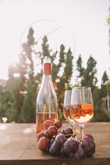 wine glasses filled with rose wine on a table next to the bottle and purple table grapes with trees in the distance photo