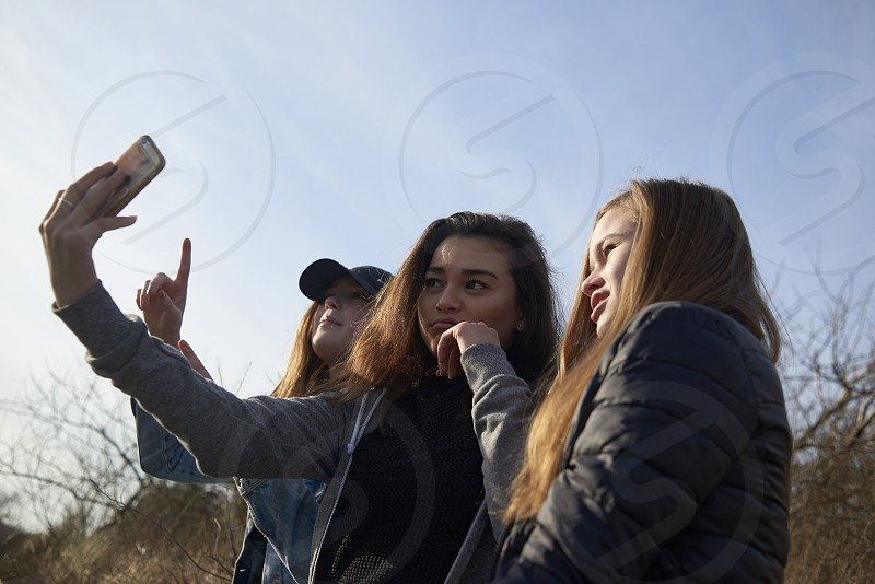 Three pretty teen girls taking a selfie together using a mobile phone sitting outside on a beautiful sunny day in autumn photo