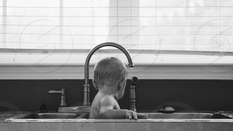 Baby bathing in the sink in black and white. photo