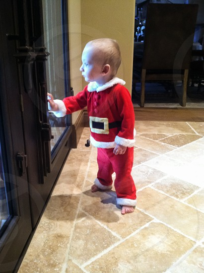 baby in red and white santa's suit standing photo
