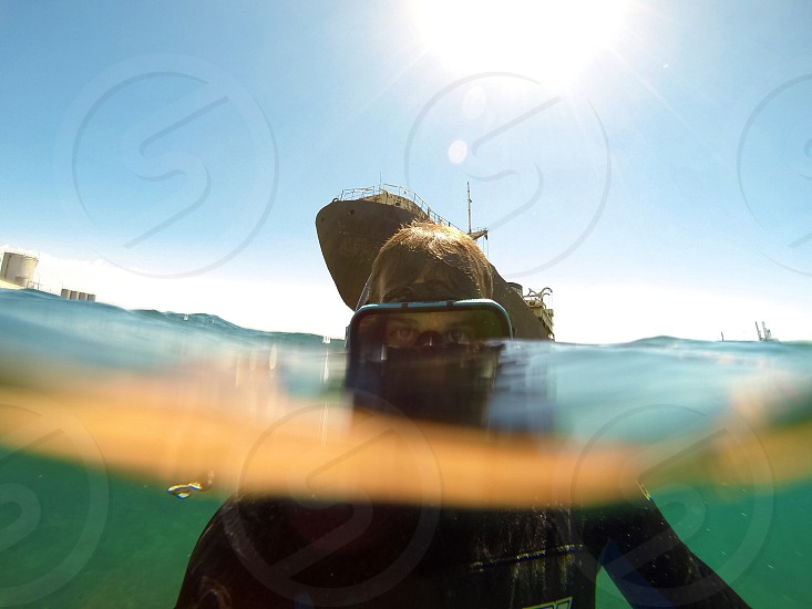 man in black goggles diving on ocean photo
