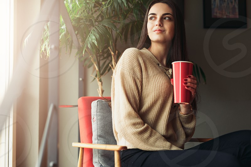 Woman sit on stairs at home smell her green tea and feels great. Green tree on background and copy space fot text photo