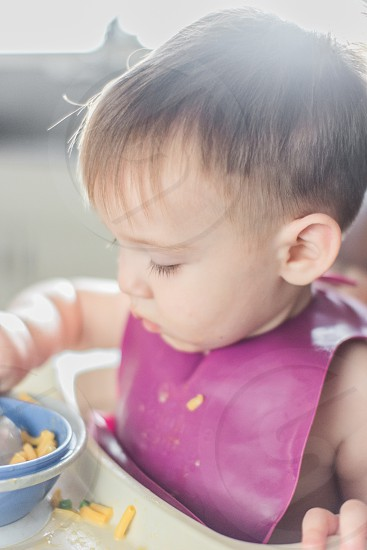 baby with brown hair wearing pink bib while eating photo