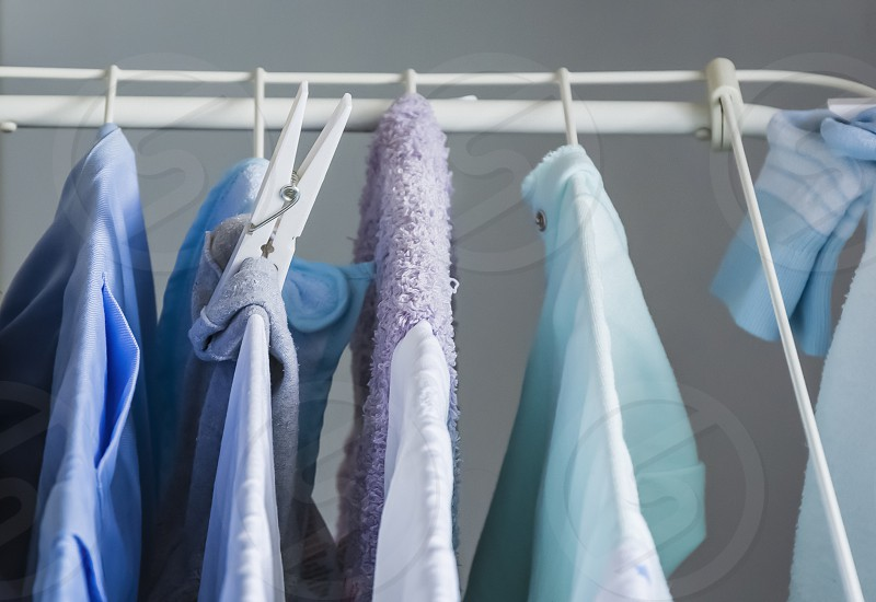 different types of clothes left hanging to dry kept by a clothespin on a clotheshorse photo