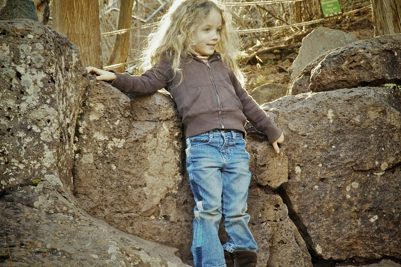 girl wearing gray jacket and blue jeans standing on rock photo