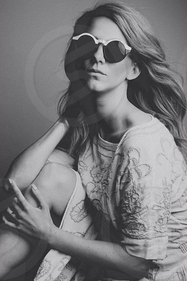 black and white photo of woman wearing black round sunglasses photo