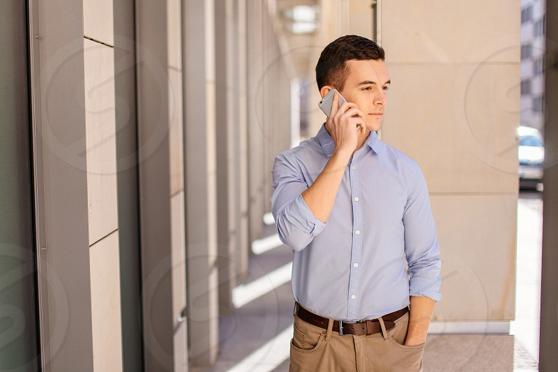 Businessman talking at his phone with friend on blur background photo