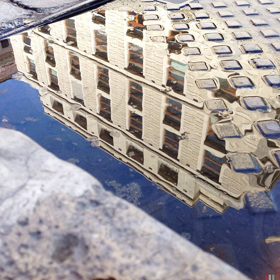 reflection of white building on water photo
