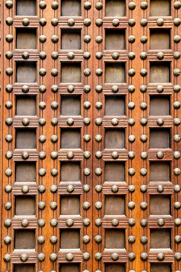 ancient church castle wooden door with nails and little square shapes in spain photo