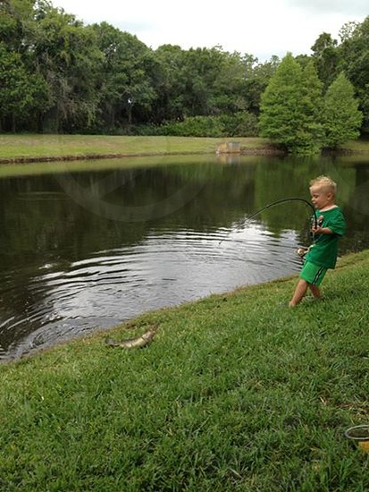 boy in green t shirt and green shorts holding fishing reel photo