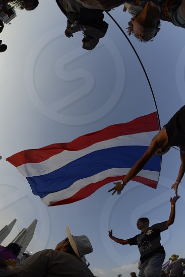 Thai anti-government protesters wave national flags during a rally at the