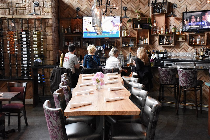 4 women sitting on purple and gray floral padded chair beside counter facing wall mounted flat screen televisions turned on with dining sets behind inside restobar photo