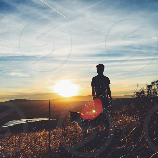 silhouette of man and dog standing on mountain under orange sunset photo