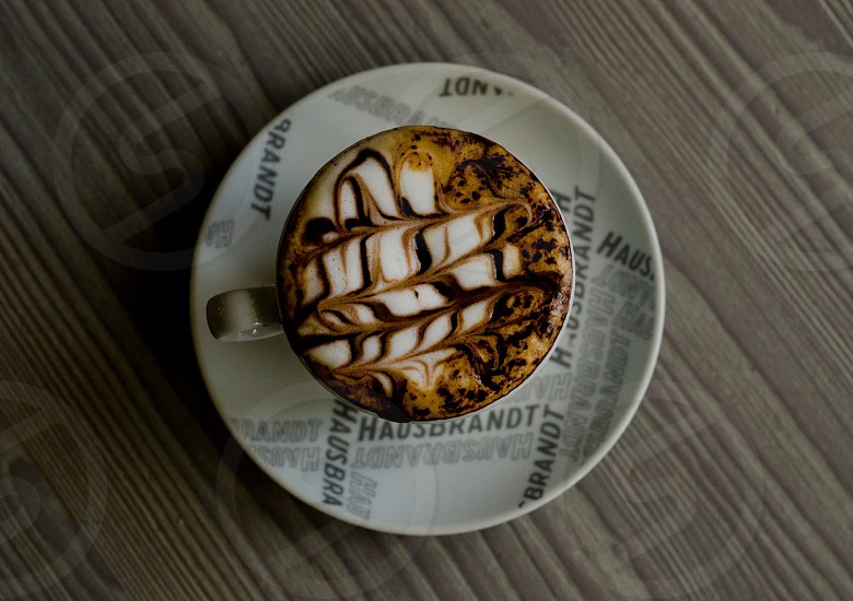 cup of coffee on saucer on top of table photo