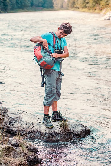 Young boy takes out outdoor mug to take pure water from a river. He is standing on a rock over the river rests during a hike spends a vacation on wandering with backpack he is wearing sport summer clothes photo