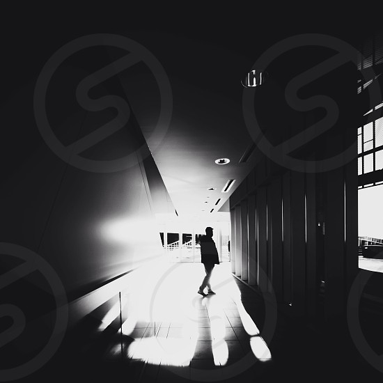 black and white photo of person standing in hallway photo