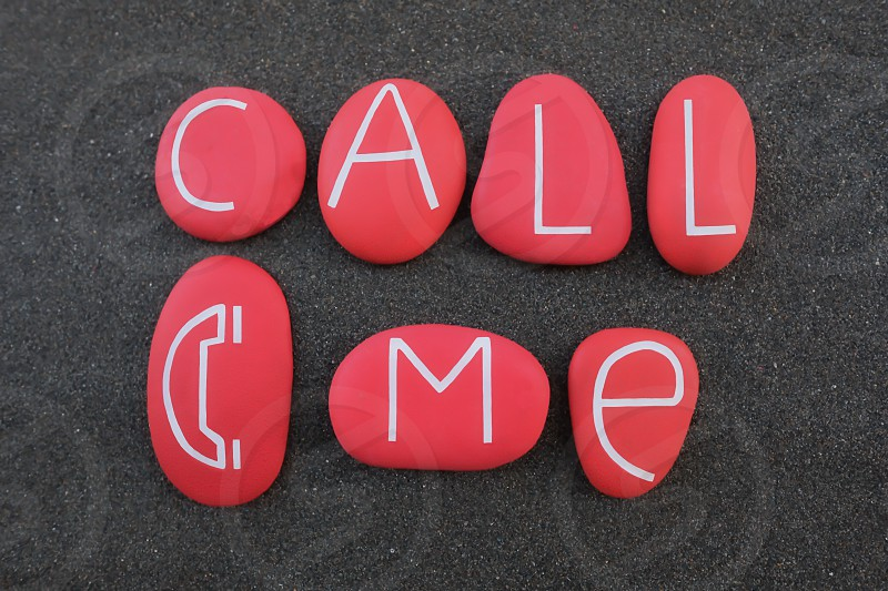 Call me concept with a creative composition of red colored and carved stones design photo