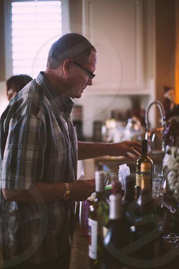 man wearing white and grey plaid print button down shirt grabbing bottle photo