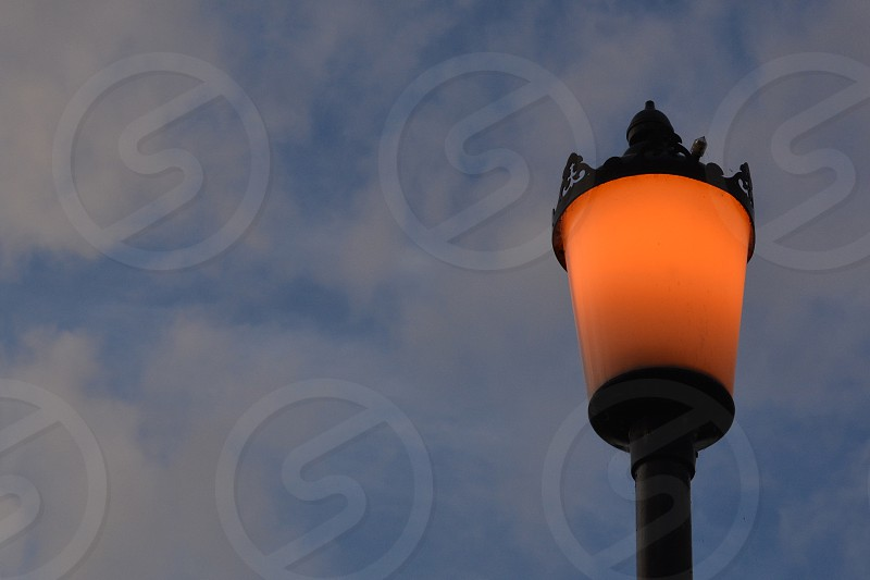 Light post at dusk orange and grey vintage electrics council savings green clouds photo