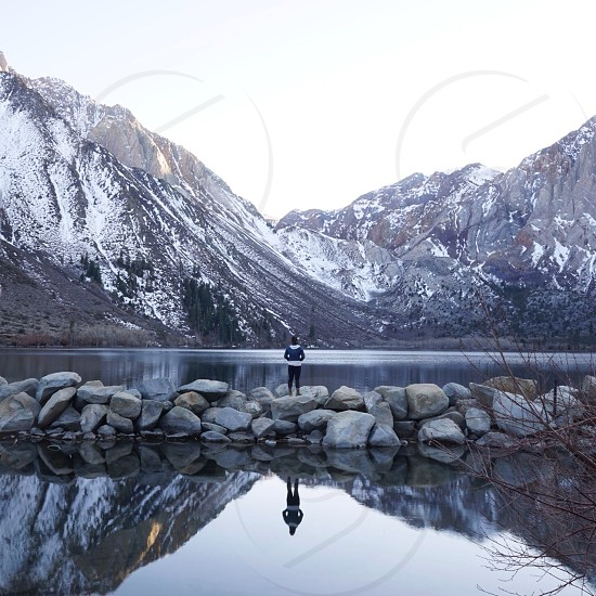 person standing in a pile of rocks in the middle of tall mountains and body of water photo