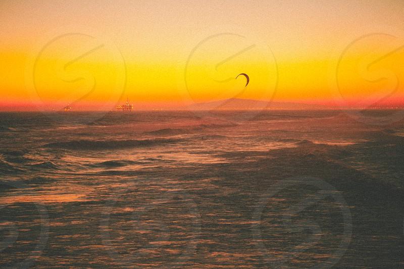 person parasailing in ocean against orange sunset photo