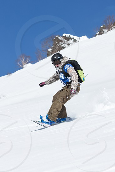 "KAMCHATKA RUSSIA - MARCH 9 2014: Girl snowboarder rides steep mountains. Competitions freeride skiers and snowboarders ""Kamchatka Freeride Open Cup"". Russia Far East Kamchatka Peninsula. photo"