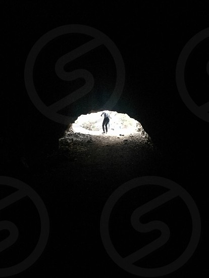 person in black pants in front of cave photo