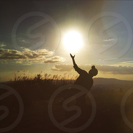 person in fitted cap holding sun in forced perspective photography photo