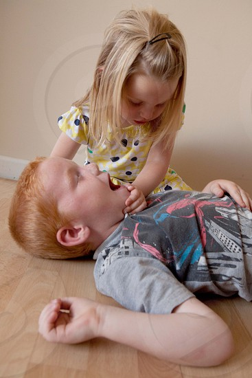 girl doing basic life support to a boy photo