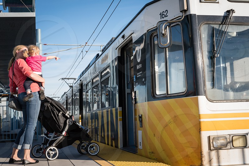 Mother with stroller and children waiting to board metro train photo
