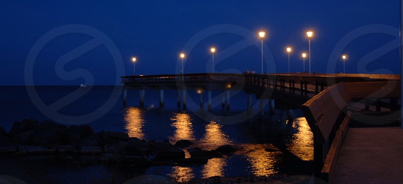 A San Francisco pier at midnight illuminated by the light posts and their reflections in the water below.  photo