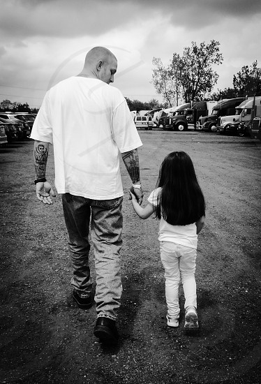 Man with tattoos holding the hand of a little girl looking down at her as they walk. photo